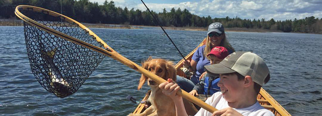 Family fishing netting a landlocked salmon