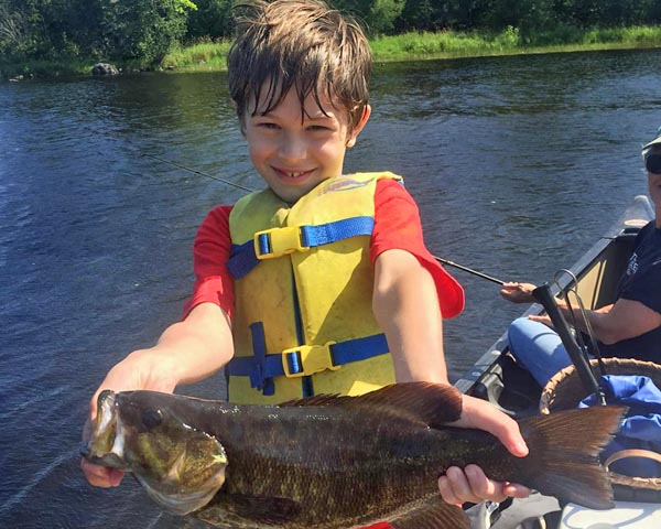 Boy learning to fish for bass in Maine