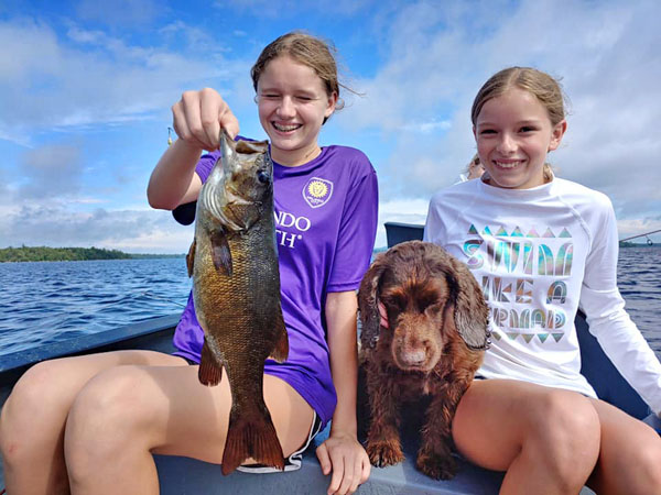 Girls catching a huge smallmouth bass in Maine